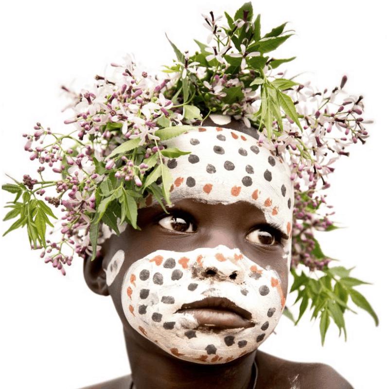 Giovanna Aryafara photography Suri Tribe. Young Suri boy with flowers